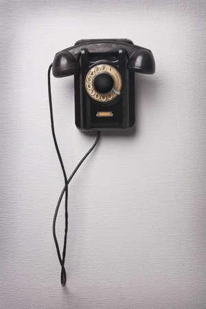 Vieux téléphone noir en rotation sur le mur