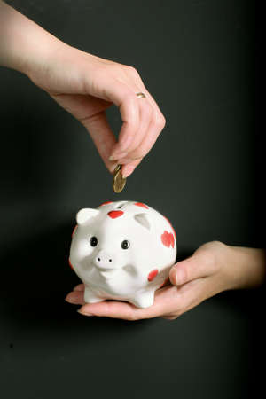 Pig-coin box in female hands on black background photo