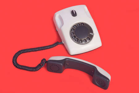 rotational: White rotational phone on red background Stock Photo