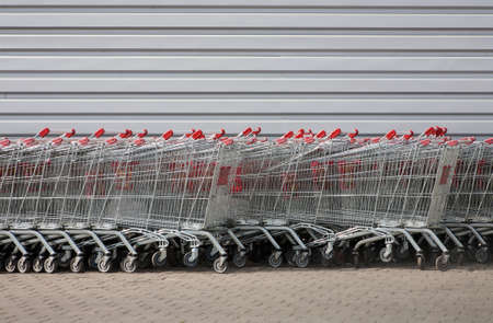 shopping carriage: number of metal carts at supermarket wall
