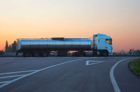 gas-tank truck with  chromeplated tank goes on road in morning