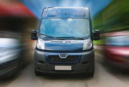 dark blue minibus goes on city street Standard-Bild