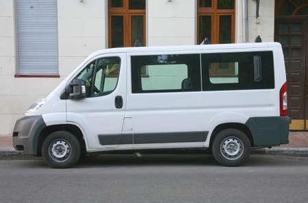 blanco minibús estacionado en calle de la ciudad