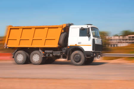 big powerful dump truck goes on road photo