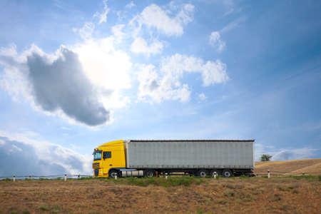 camión auto grande va en el camino hacia el cielo de fondo Foto de archivo