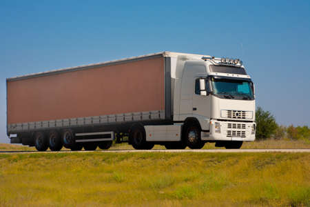 transporter: big auto truck goes on the way to sky background Stock Photo