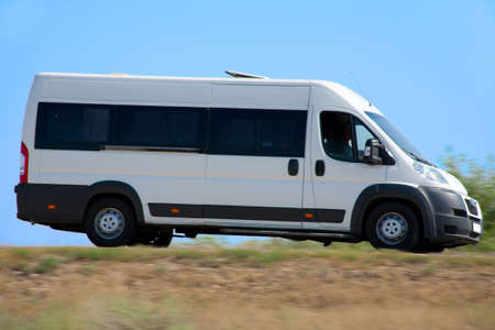 country highway: white minibus goes on country highway