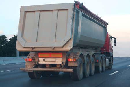 camion à benne grande va dans la soirée sur l'autoroute