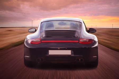 роскошный спортивный автомобиль идет по пути снижения фона Редакционное