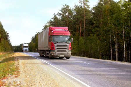 motorway: Two trailers go on highway along wood Stock Photo