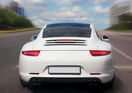 white prestigious car goes on city street  Standard-Bild