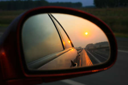 Sunset in mirror of car going on road Stock Photo - 15256317