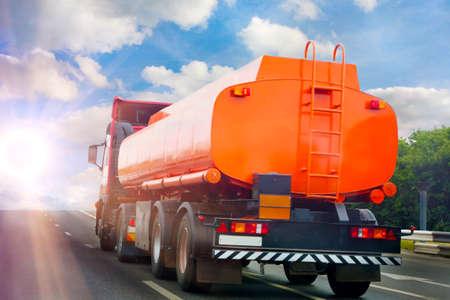большой бензобак грузовика идет по шоссе на фоне неба