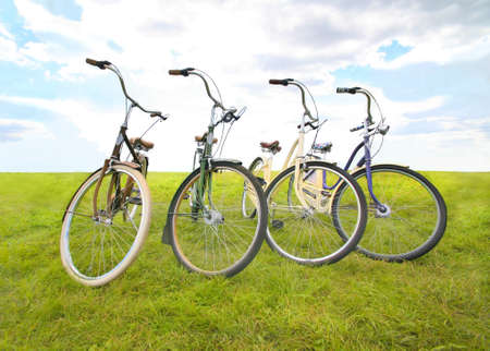four bicycles on meadow against the sky Stock Photo - 16161832