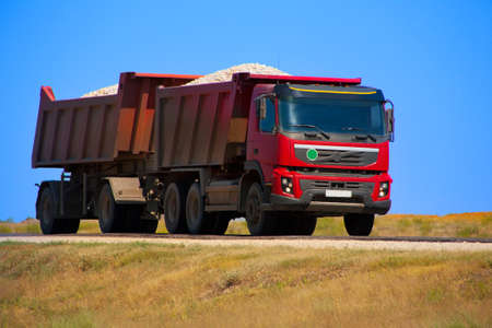 payload: red dump truck with the trailer loaded with rubble