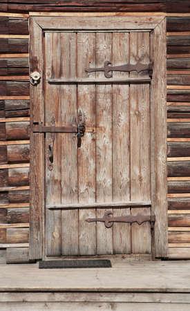 wooden door in wall of an old log house Standard-Bild