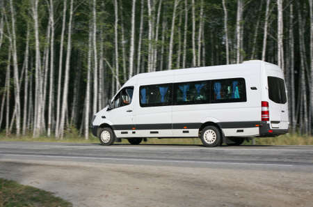 mini bus:  white minibus goes on the forest road
