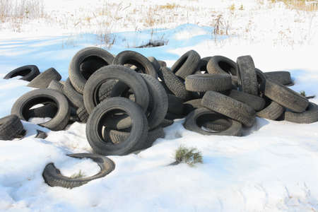 junk yard: rubber tires dumped on snow in the field