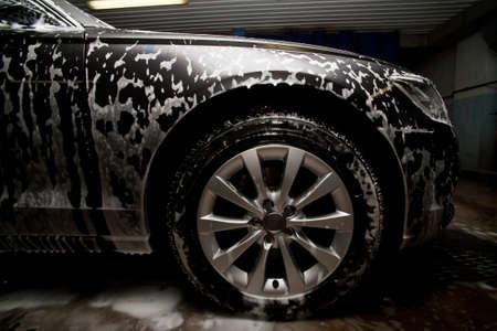 prestigioso coche nuevo negro de espuma en el fregadero Foto de archivo