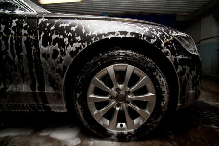 prestigious new black car in foam on sink photo