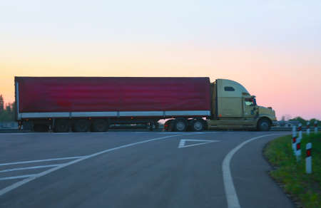 big trailer goes on  motorway against sunset photo