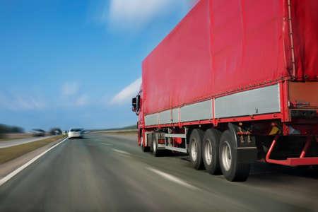 Прицеп с красным тентом движется с большой скоростью по шоссе