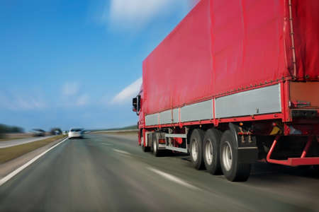 trailer with red awning moves at high speed on the highway Standard-Bild