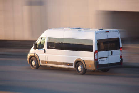 quickly: white minibus quickly goes on the highway