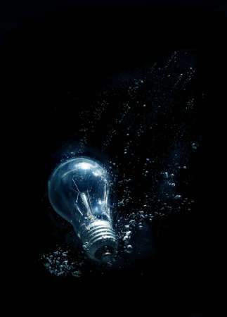 light source: bulb in water with bubbles on black background Stock Photo