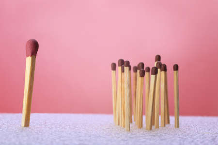 wooden sulfuric matches vertically on red background photo