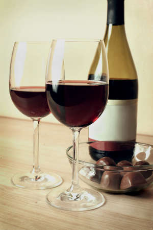 two glasses of red wine and chocolates on table photo