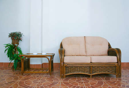 luxus: sofa and rattan table in an interior against wall