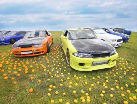 field glass: bright colour cars and fruit on grass