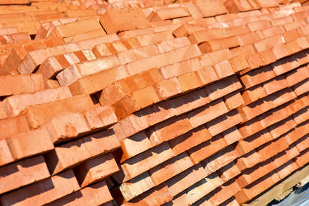 red bricks laid in pallets outside photo
