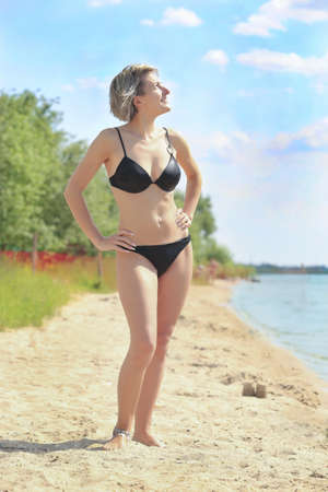 beautiful slender woman in bikini on beach photo