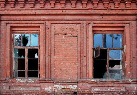 window frames with the broken glasses on an old brick wall photo