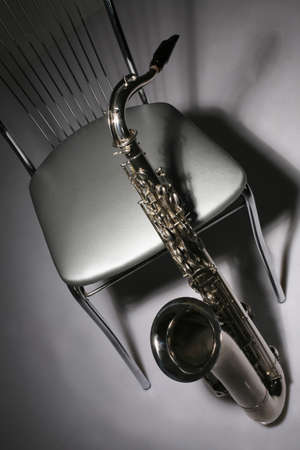 tenor: musical instrument saxophone and chair against dark background