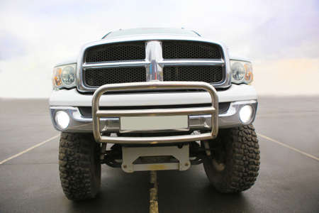 face off: big white SUV with big wheels
