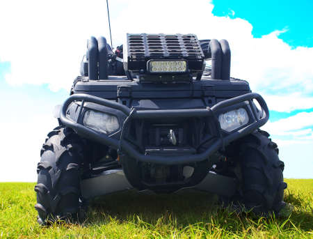 four wheel drive: powerful black ATV frontally on grass