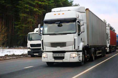 camions vont sur la route en hiver contre le bois