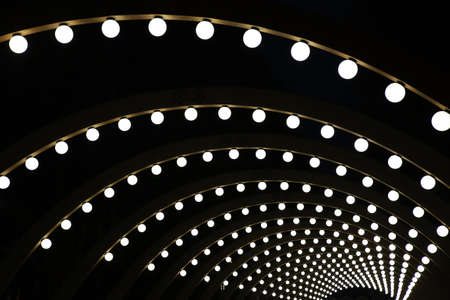 lighting equipment: wooden arches with spherical shining lamps against dark background