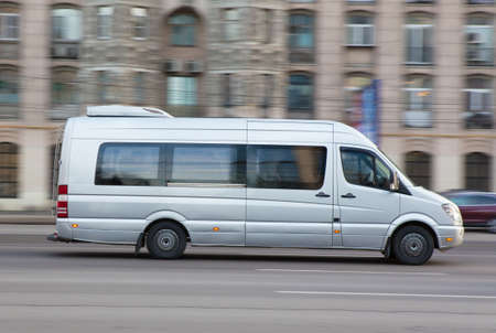 minibus: silvery minibus goes down the street the cities Stock Photo