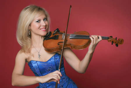 woman violinist in blue dress on red  photo