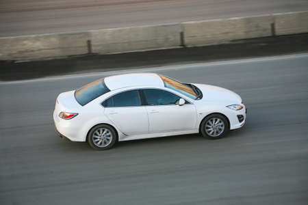 cornering: modern white car driving on city street Stock Photo