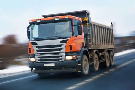 volteo: camión de volteo con una cabina de naranja va en la carretera en el invierno