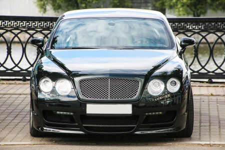 front bumper: black luxury  car parked on the embankment near parapet
