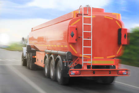 big gas-tank truck goes on highway against the sky photo
