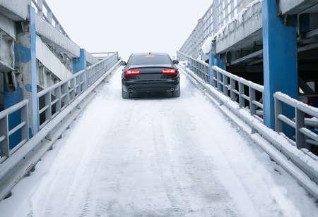 moderne zwarte prestigieuze auto op vele niveaus parkeren in de winter Stockfoto