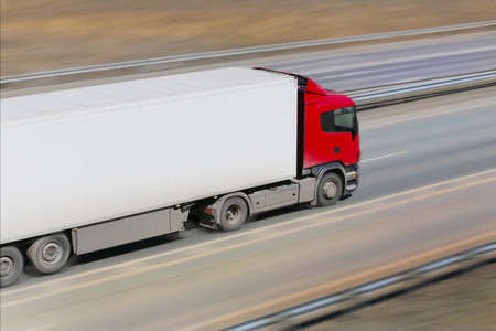 trailer with red awning moves at high speed on the highway Stock Photo