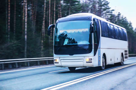 white tourist bus moves on the country highway Standard-Bild